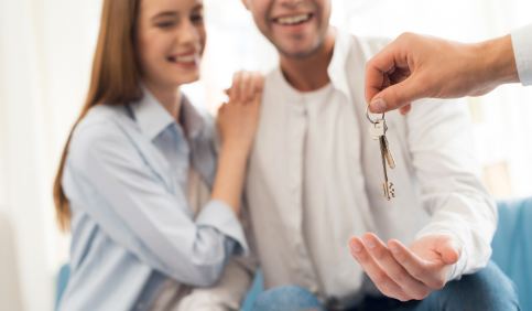 REALTOR® handing a young couple a set of keys to their new home