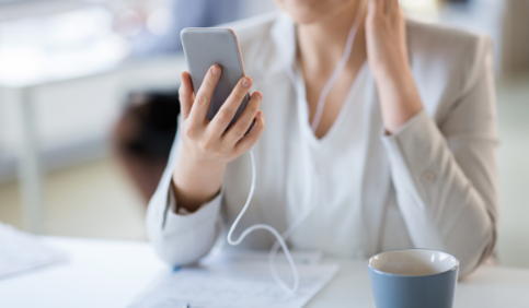 Businesswoman with earphones and smartphone at office