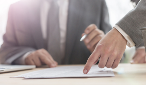 Hand of business woman pointing at document to senior businessman in office