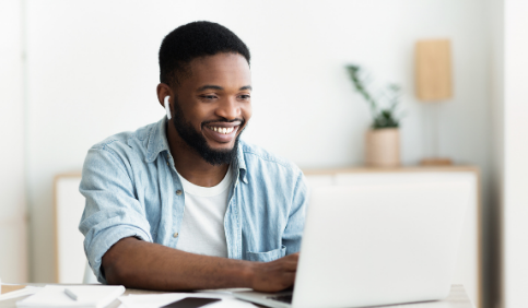 Smiling African American man in earphones studying foreign language online