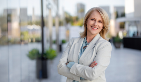 Smiling business woman with hands crossed outside corporate office